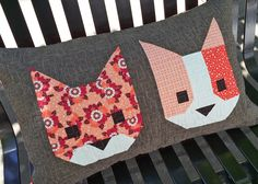 """Cat Friends is a fun 16"""" x 26""""pillow project made using two blocks from  The Kittens quilt pattern. The Kittens includes five different cat face  blocks and two glasses appliqué patterns, so you can have fun mixing and  matching your favorite cat friends.  Personally, I think it would be fun to make blocks that resemble actual  cats and will have to get around to making one with cats that look like  George-Michael and Maeby! (my two cats)  The samplepillow was made using fabric from my…"""