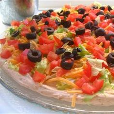 Taco Dip I Recipe Appetizers with cream cheese, non-fat sour cream, taco seasoning mix, iceberg lettuce, shredded cheddar cheese, chopped tomatoes, green bell pepper, black olives