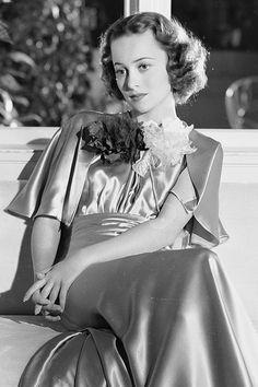 Olivia de Havilland rests on a window seat in a full-length satin dress, 1936