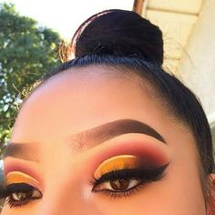 Crimson red, yellow liner and winged eye liner. Glam colorful makeup look.