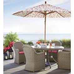 Romantic curves in handwoven 100% recyclable resin wicker bring back the nostalgia of garden hospitality. Hand-loomed around weather-resistant powdercoated aluminum frames, Summerlin's tonal weathered-grey weave captures the true nature and patina of real cottage wicker, only better with UV- and weather-resistant properties. Graceful round dining table is topped in clear tempered and polished glass.