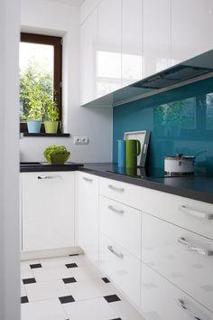 Turkusowy lacobel nad blatem ożywia wystrój kolorem, a do tego odbija światło, powiększając przestrzeń / White kitchen with turquoise highlights.