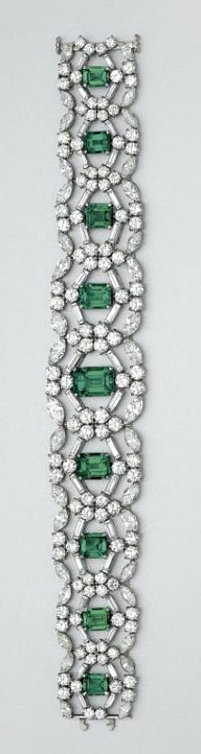 EMERALD AND DIAMOND BRACELET, CARTIER The highly flexible openwork band set with 9 emerald-cut emeralds weighing approximately 14.00 carats, within stylized circular frames set with 108 round, 36 baguette and 36 marquise-shaped diamonds, altogether weighing approximately 26.00 carats, mounted in platinum, length 7 inches, signed Cartier, numbered 914751. With red leather Cartier box.