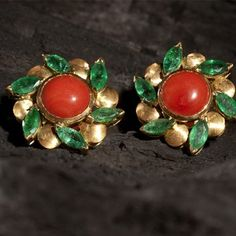 Orange Corals surrounded by fine quality emerald marquise with a brushed finished in 18k yellow Gold.