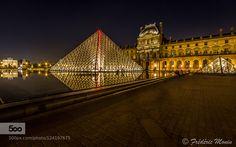 Le Louvre by night Pyramide du Louvre située au centre de la cour Napoléon à Paris. Au second plan on aperçoit l'arc de triomphe du Caroussel.