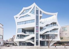 Concave walls give a scalloped outline to this mixed-use block in South Korea.