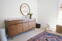 mid century modern nursery. vintage persian rug. eclectic. pottery barn bear rocker. ubbi. modern. chic. bamboo blinds. clean. minimalist.