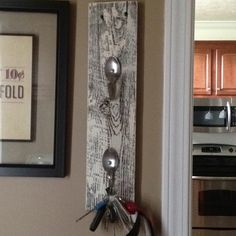 Key Hook- I made this with a piece of barn wood ad old spoons. I white washed the barn wood then with the help of my hubby punched holes in the spoons with a drill press. I used pliers to bend the spoons, then we screwed them into the wood.