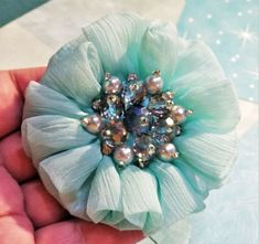 FF-156; A Turquoise Flower Made of Ruffled Chiffon Material and Accented in the Center with Faceted Clear Glass and Pearlized Beads. Turquoise Flowers, Light Turquoise, Chiffon Material, Chiffon Ruffle, Upcycled Crafts, Craft Items, Flower Making, Clear Glass, Brooch