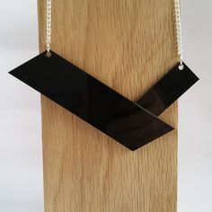 Simplicity is key with this minimal necklace. Black perspex is cut into clean, simple lines to create a necklace with understated elegance. The black pendant hangs from a silver plated curb chain
