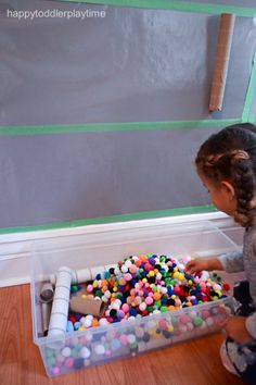 This pom pom drop activity for toddlers and preschoolers is simple to set up and great for developing problem solving, fine motor control and understanding cause and effect.