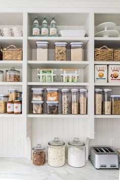 Organize to perfection, this expansive white pantry features white shelves stacked against a white beadboard backsplash and boasting glass vintage snack jars, white baskets, woven baskets, and various XO storage containers. Kitchen Organization Pantry, Home Organisation, Kitchen Pantry, Organization Hacks, Kitchen Storage, Kitchen Decor, Kitchen Cabinets, Kitchen Ideas, Kitchen Island