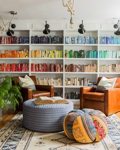 bookshelves organized by color.  Rainbow colored books with white walls and shelves.  Comfy library or living room with over-sized ottoman, chairs and beanbag chair