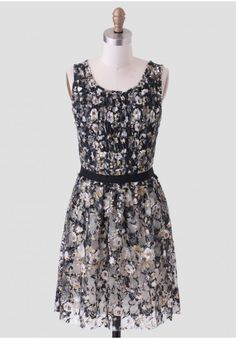 Spend an evening with this lovely black lace dress adorned with a rose print in hues of cream, gold, and light brown. Finished with small ruffles throughout the bodice and a black grosgrain ribbon at the waist, this elegant dress can be styled with metallic heels for an upscale occasion.