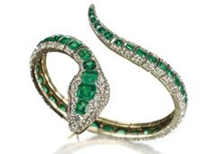 AN ANTIQUE EMERALD AND DIAMOND BANGLE   The open sprung bangle designed as a snake, the pavé-set rose-cut diamond body enhanced by a central line of rectangular-cut emeralds, the head set with circular-cut diamonds and ruby eyes, mounted in gold, mid-19th Century