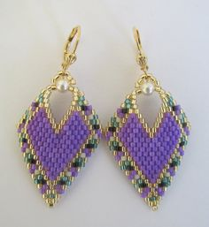 These earrings are my own original pattern. Copyright 2016 Patti Ann McAlister  These pretty earrings are slightly concave & are handmade with opaque purple, opaque black, matte bone, silver-lined teal green, & golden delica seed beads, with 4mm cream Swarovski glass pearls. They measure just about 2 long including the leverback earwire, & just about 1 wide.