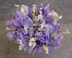 lavender sweetpea & lily of the valley bridal bouquet    Feathery lavender sweet pea and delicate lily of the valley combine in this bride's bouquet to invoke the very essence of spring. Perfect for an early spring wedding when both flowers are in season. Wedding flowers designed by our favorite Denver Wedding Florist: