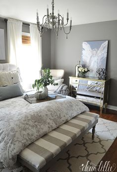 Adding a pillow and throw we found at @homegoods with a little blue to them helps pull out the blue from the painting and adds a hint of color to this gray guest bedroom. (sponsored pin)