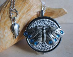 Silver Butterfly music box locket, round locket with music box inside, in silvertone with filigree and butterfly adorning front cover.