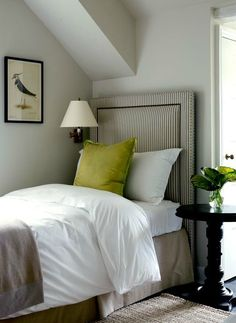 Wonderful use of space in expanded attic bedroom. Wall sconce and bed looks great against the wall. Love the ticking stripe headboard  and the pop of lime!