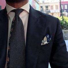 Peak lapel navy suit, white shirt, floral and dotted navy tie, white floral silk p square