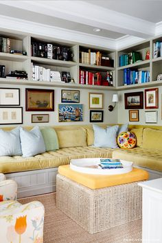 Sag habor - built-in seating area. Bookshelves up to the ceiling with books arranged by color, gallery wall below - great styling. yellow fabric lemon