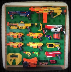 Nerf Gun Wall!  Awesome way to display and store our Nerf Gun collection. They're all loaded, ready to grab 'n go, with spare clips and darts in the baskets below.