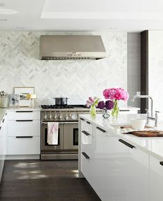 These glossy white beauties are from Ikea (Akurum Abstrakt) and are accented with angular dark bronze pulls from Rocky Mountain Hardware. The showstopping herringbone marble backsplash is fashioned out of 2- by 8-inch Calacatta Michelangelo tiles. HanStone quartz (Aurora Snow) covers the countertops.