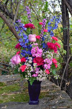 Irresistible Gillespie Florists - Indianapolis, IN The Irresistible bouquet is created with blue delphinium, purple liatris, lavender roses, hot pink mini carnations, plum carnations, wax flower, lavender stock and baker's fern in a cobalt blue couture vase!