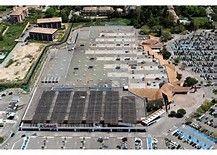 """Enseigne """"Géant"""" > Parking et centre commercial descendus du Ciel > 1) Dégager - 2) Aplanir - 3) Faire atterir les matériaux de construction (taules, béton, plaques isolantes, bitume, palissades préfabriquées, etc.). Bing images"""