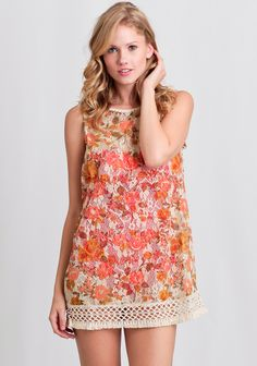 This stunning sheer lace cover-up tunic features a rust, mustard, and olive green floral print allover with a cream-colored crochet hemline.