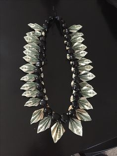 Money Lei great for a man. Dollar bills are folded in the shape of leaves and tied to a kukui nut necklace.
