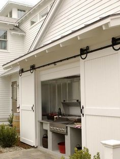 Built in Grill carriage house sliding doors. (I want this in my dream home! What a great way to keep an outdoor kitchen out of the elements!)
