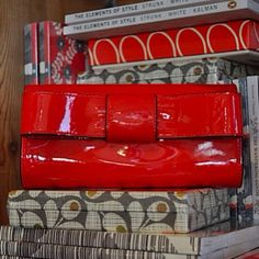 Make a happy statement with this Orla Kiely raspberry red glossy patent wallet with bow detail $198.    The Children's Hour Bookstore & Boutique    Clothing  Gifts  Toys  Shoes    898 South 900 East    Salt Lake City Utah    801.359.4150    childrenshourbookstore.com