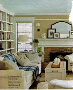 Mantle, Couch/Bookshelf, white sofa with cozy plaid blanket, white trunk table, candles, wood, brick, neutrals, pretty shaped mirror. Comfortable and cozy!