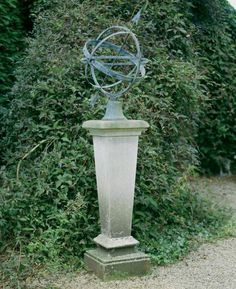 An inverted limestone pedestal with bronze armillary sphere,