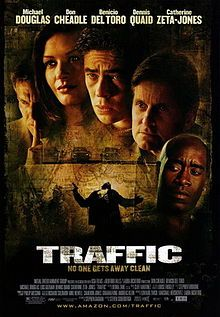 Film poster with five people shown from the neck up. The man on the left has his pointer finger pressed against his lips; the woman to his right has long hair and is smiling; the three man at the right have grim looks as they stare to the right. Below them are several vehicles and a man holding a gun that is getting shot. The top of the image includes the starring credits, while the bottom includes the title of the film and the main credits.
