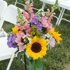 Beautiful Summer Bouquet With Sunflowers, Pink Snapdragons, Purple Stock and Accent Flowers In a Large Blue Mason Jar.  We Tied These to Shepard Hooks to Line the Aisle.  Click To See More From This Wedding.