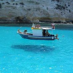 This picture is taken on One House Bay in Greece. The water is so clear that the boat seems to be floating on air!