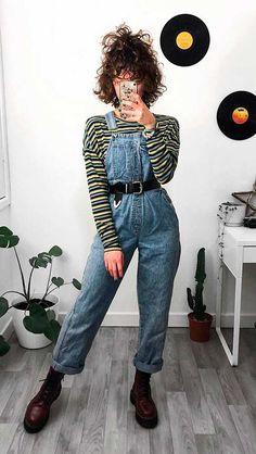 10 ideias de sobreposição para testar nessa temporada - #GuitaModa. Blusa de manga com listras coloridas, jardineira jeans com cinto preto, coturno vinho