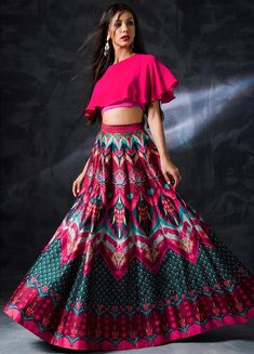 A multicoloured lehenga with abstract print in the shades of turquoise blue and fuschia pink. Moreover, teaming it with a unique cape-style hot pink blouse gives the outfit a perfect finishing. Hot Pink Lehenga with abstract print Indian Fashion Dresses, Indian Bridal Outfits, Indian Gowns Dresses, Dress Indian Style, Indian Designer Outfits, Fashion Outfits, Trendy Outfits, Bridal Dresses, Choli Designs