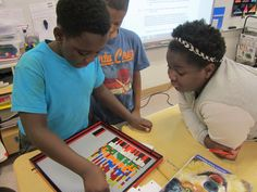 BJ adding his LEGO button to the homework chart with Ariana looking on.