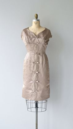 Vintage 1950s shimmery taupe silk cocktail dress with wide wrap neckline, cap sleeves, empire bust with small bows traveling the length of the dress,