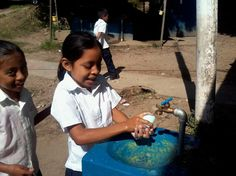 """""""Now (after Project WET's project) they practice healthy habits in this manner."""" Students enthusiastically lather up their hands with soap and fresh water at a small sink with a tap."""