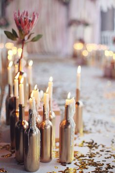 Gold painted wine bottles. Use real wax on the bottles then use led tapers for safety.