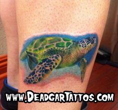 Sea turtle tattoo with water behind it