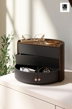 $53 · Moona features round, circular shapes for a one-of-a-kind jewelry organizer. Both decorative and functional, Moona has a large display top that doubles as a tray for smaller accessories, perfume, small plants or other items. Its three rotating drawers can provide hidden storage or be pushed out for easy access. With its unique semi-circle shape and beautiful wood accents, Moona can be displayed on your vanity, counter, dresser, desk and more. Jewellery Storage, Jewelry Organization, Thoughtful Gifts For Her, Modern Jewelry Box, Gift Wrapping Services, Wood Home Decor, Small Plants, Hidden Storage, Dorm Decorations