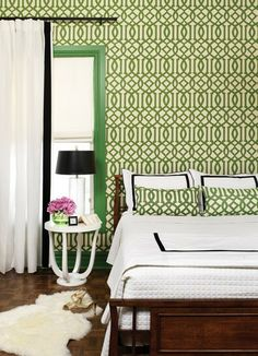 Bedroom, White linens, Black trim, White side table, Green patterned wallpaper, White curtains with black ribbon banding, Sheepskin, Wood bedframe