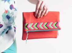 This medium fold over clutch is made from a linen blend in punchy orange coral. Under the fold is an velcro slot pocket which would be perfect for holding your phone and other goodies. For an added pop of colour there are bright ribbon details. It is lined with teal cotton and a matching nylon zipper will keep all your treasures securely inside. The bag has been interfaced with a fusible fleece for extra structure and padding. The perfect bag for keeping all of your essentials organized…