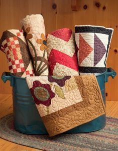 Set the tone of a room with several quilts that use the same theme; a ...